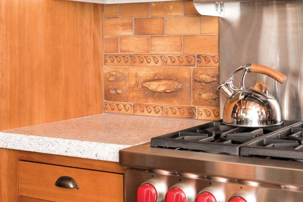 The kitchen's custom splash tiles depict game fish to memorialize the generations of lake fishermen that would bring home their catch.