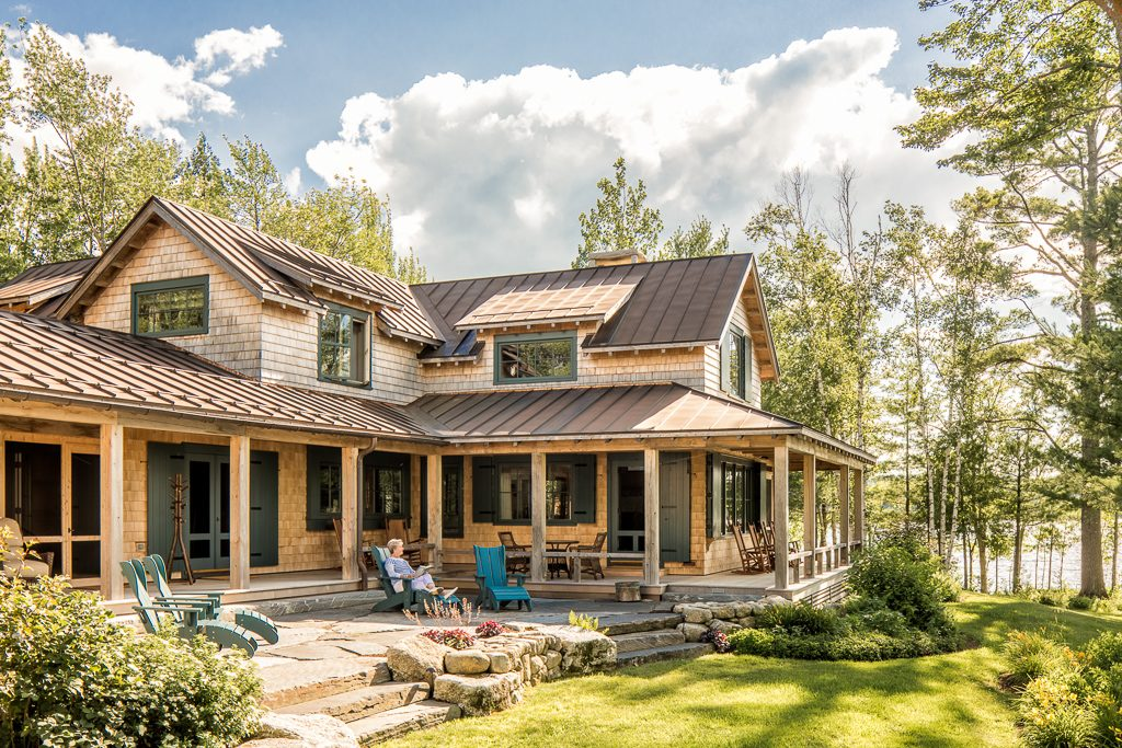 The roofs of this lake house renovation are red copper standing seam, the shingles are eastern white cedar, and all the posts on the porch are of solid eastern white cedar.