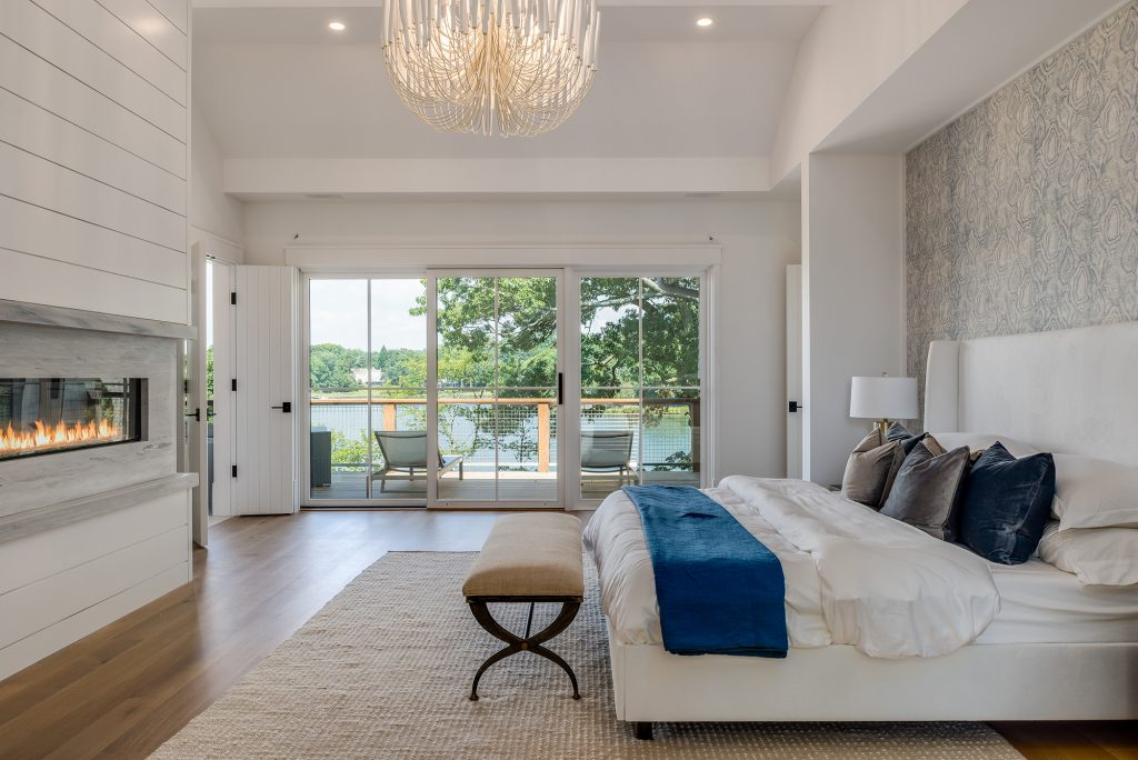 Shiplap walls adorn the master suite along with a modern gas fireplace and a large wooden chandelier. The Phillip Jefferies wallpaper integrates a muted, oyster shell pattern represent the oyster beds found in the nearby pond — which can be seen from the private deck.