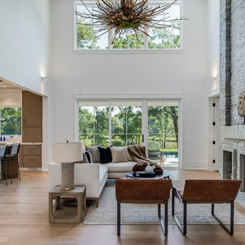 The spectacular, two-story family room features a floor-to-ceiling, stone hearth and custom-made, native driftwood chandelier. The room opens up onto its own private porch with remarkable views.