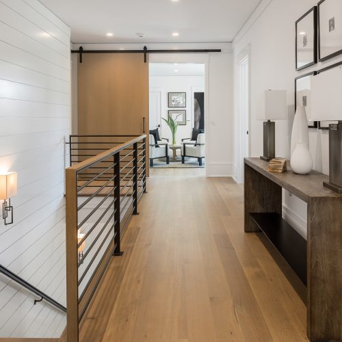 A custom-built steel railing lines the second-floor landing, which leads to a loft with an oversized barn door.