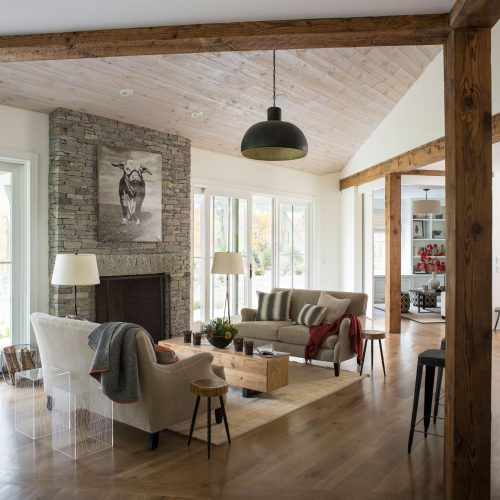 A floor-to-ceiling, split-face, stone fireplace graces the airy, open-plan family room.