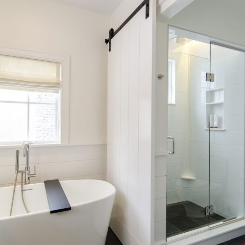 The master bathroom with a soaking tub has a direct line of sight across the meadows to a historic red barn.