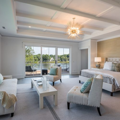 The master bedroom is designed feel like a hotel suite with multiple water views and a deck overlooking the backyard, pool, gardens and pond.